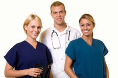 Medical team. Two woman healthcare workers with one male in the middle wearing a doctors lab coat Stock Photos