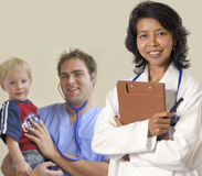 Medical team. Smiling and conident female Asian Doctor and male intern holding child Stock Images