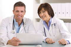 Medical team. Of male and female doctors sitting at desk Stock Images