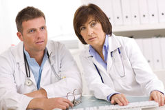 Medical team. Of male and female doctors sitting at desk Royalty Free Stock Photos