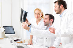 Medical team analysing together a x ray at the hospital Stock Photo