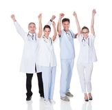 Medical team celebrating success. Diverse medical team of male and female doctors and nurses celebrating a successful outcome to a case Stock Photography