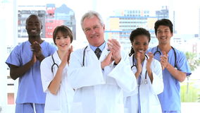 Medical team clapping their hands Royalty Free Stock Photo