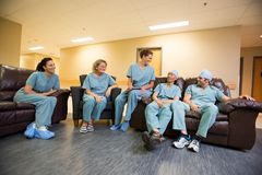 Medical Team Conversing In Hospital's Waiting Room Royalty Free Stock Image