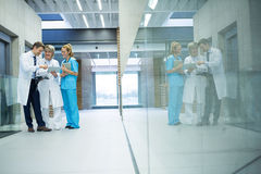 Medical team discussing over digital tablet in corridor Royalty Free Stock Photography