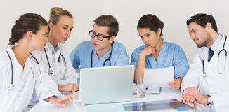 Medical team discussing over laptop Royalty Free Stock Image