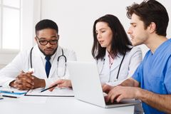 Medical Team Discussing Reports, Using Laptop At Meeting royalty free stock image