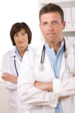 Medical team - doctors. Portrait of medical doctors male and female at office. Focus on woman Royalty Free Stock Image