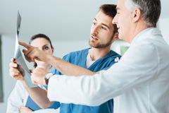 Medical team examining patient's x-ray Stock Photos