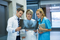 Medical team examining x-ray report in corridor. At hospital Stock Images