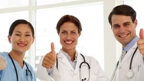 Medical team giving thumbs up to camera Royalty Free Stock Photo