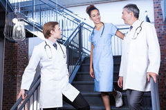 Medical team interacting with each other on staircase Royalty Free Stock Photo
