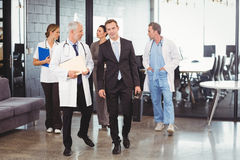 Medical team interacting each other while walking together. In hospital Royalty Free Stock Image