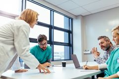 Staff briefing in hospital boardroom. Medical team interacting at a meeting. Medical staff meeting in conference room stock image
