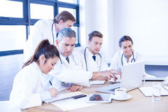 Medical team looking into laptop and having a discussion Stock Photo