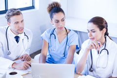 Medical team looking into laptop and having a discussion Stock Photos