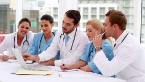 Medical team looking at laptop during meeting stock video