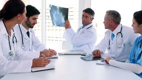 Medical team looking at x-ray during a meeting stock footage