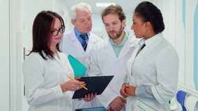 Medical team looks at clipboard. Multiracial medical team looking at the clipboard in woman`s hand. Attractive caucasian female doctor in glasses explaining stock video footage