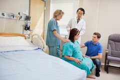 Medical Team And Man Looking At Pregnant Woman In Royalty Free Stock Photography