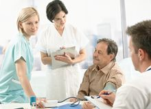 Medical team measuring blood pressure. Of senior patient, nurse assisting, doctors taking notes on clipboard Royalty Free Stock Images