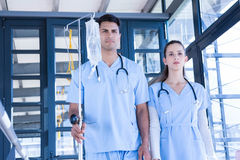 Medical team in medic uniform with saline stand Stock Photography