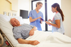 Medical Team Meeting As Senior Man Sleeps In Hospital Room Royalty Free Stock Photos