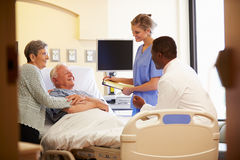 Medical Team Meeting With Senior Couple In Hospital Room. Medical Team Meeting With Happy Senior Couple In Hospital Room Smiling At Each Other Royalty Free Stock Images