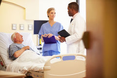 Medical Team Meeting With Senior Man In Hospital Room Royalty Free Stock Photos