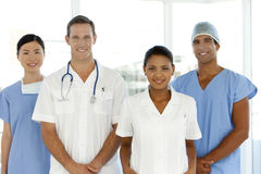 Medical team. Portrait of a multi-ethnic medical team including Caucasian, Asian, Afro-American and Indian members. They stand in a row. They are all young but Stock Images