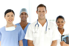 Medical team. Portrait of a multi-ethnic medical team including Caucasian, Asian, Afro-American and Indian members. They stand in a row with white men as leader Royalty Free Stock Images