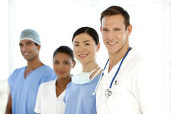 Medical team. Portrait of a multi-ethnic medical team including Caucasian, Asian, Afro-American and Indian members. They stand in a row with white men as leader Stock Images