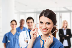 Medical team. Portrait of a smiling nurse in front of a medical team Royalty Free Stock Photography