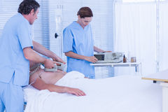 Medical team resuscitating a man with a defibrillator Royalty Free Stock Photo