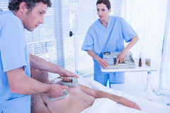 Medical team resuscitating a man with a defibrillator. Medical team resuscitating a men with a defibrillator in hospital room Stock Image
