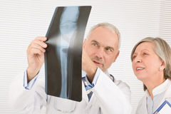 Medical team senior doctors look at x-ray stock photography