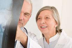 Medical team senior doctors look at x-ray Stock Photo