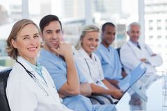 Medical team sitting in row. And looking at the camera royalty free stock image