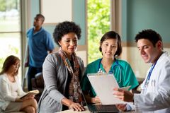 Medical team talking with patients. Medical team talking with a patient in the doctors office Royalty Free Stock Photo