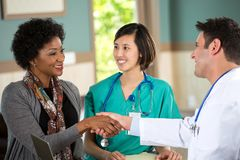 Medical team talking with patients. Medical team talking with a patient in the doctors office Stock Photo