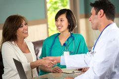 Medical team talking with patients. Medical team talking with a patient in the doctors office Stock Image