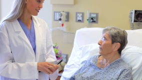 Medical Team Talking To Senior Female Patient In Hospital stock video footage