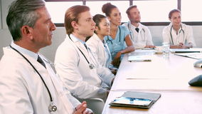 Medical team talking together while applauding stock footage