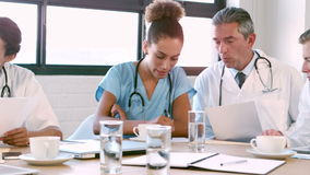 Medical team talking together while looking folder stock footage