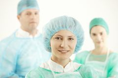 Medical team in uniform. Female doctor smiling at camera, colleagues in background royalty free stock photography