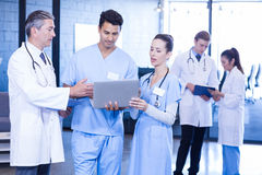 Medical team using laptop, digital tablet and examining medical report Royalty Free Stock Images