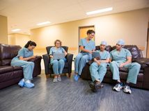Medical Team Using Technologies In Hospital's. Full length of surgeons and nurses using technologies in hospital's waiting room Royalty Free Stock Images