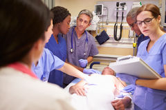 Medical Team Working On Patient In Emergency Room. With Nurse Reading Records royalty free stock photos