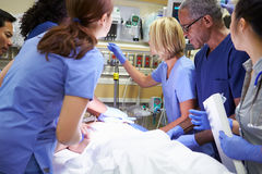 Medical Team Working On Patient In Emergency Room. Wearing Scrubs Using Medical Equipment stock photo
