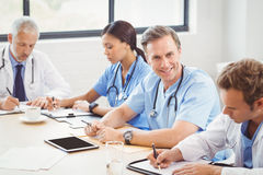Medical team writing a report in conference room Stock Photos